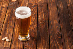 Glass of light cold frothy beer, nuts old wooden table. Glass of light cold frothy beer, nuts on an old wooden table Royalty Free Stock Photography