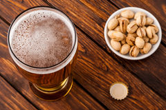 Glass of light cold frothy beer, nuts old wooden table. Glass of light cold frothy beer, nuts on an old wooden table Stock Images