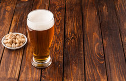 Glass of light cold frothy beer, nuts old wooden table Stock Photo