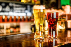 Glass of light and dark beer on a pub with bokeh background Stock Photo