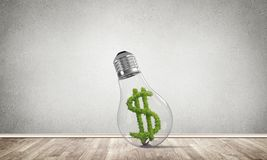 Concept of effective business innovations. Glass lightbulb with green dollar symbol inside in empty room with grey wall on background. 3D rendering Royalty Free Stock Photos