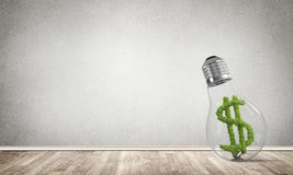 Concept of effective business innovations. Glass lightbulb with green dollar symbol inside in empty room with grey wall on background. 3D rendering Royalty Free Stock Images