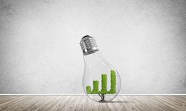 Concept of effective marketing innovations. Glass lightbulb with growing green graph inside in empty room with grey wall on background. 3D rendering Royalty Free Stock Images