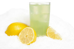 Glass of lime juice with ice cubes,lemons on snow on white Royalty Free Stock Photo