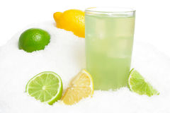 Glass of lime juice with ice cubes,limes and lemons halves on snow on white Royalty Free Stock Photos