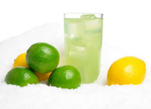 Glass of lime juice with ice cubes,limes,lemons on snow on white Stock Images