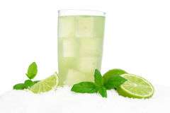 Glass of lime juice with ice cubes on snow on white Stock Photos