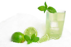Glass of lime juice with ice cubes on snow on white Stock Photography