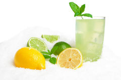 Glass of lime juice,lemons,ice cubes on snow on white Stock Image