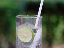 Glass of lime juice. With white straw at the summer garden. Close up Royalty Free Stock Image