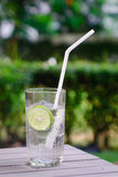 Glass of lime juice. With white straw on wooden table at the summer garden. Close up Stock Photos