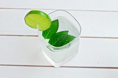 Glass of lime juice on white wooden table Stock Images