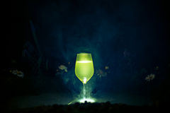 A glass with limoncello on a dark background and smoke royalty free stock photos