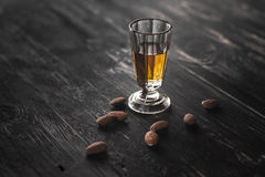 A glass of liqueur and almonds Royalty Free Stock Photography
