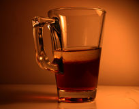 Glass with the liquid. A glass with the liquid, lightened and strongly toned Stock Photo