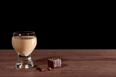 Glass with liquor, candy and coffee beans on a black background. Stock Photos