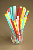 Glass with lot of long color cocktail straws Stock Photos