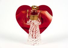 Glass made angel reading. Heart shape red greeting card with love sign made by hands behind it.  stock images
