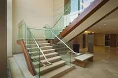 Glass and mahogany staircase. Staircase leading to 2nd floor in modern office building Stock Image