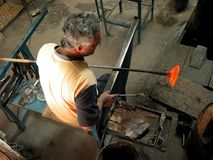 Glass making artisan in his workshop. Skilled middle aged glass maker surrounded by his trade tools busy manufacturing a hand made glass bowl in his workshop in Royalty Free Stock Images