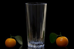 Glass and mandarins Stock Images