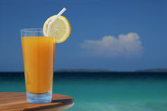 Glass of Mango Juice with Straw and Lemon Twist. Glass of Juice with Lemon Twist and Straw Against Tropical Sea stock photo