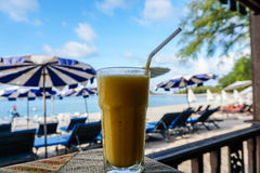 Glass of mango shake with sea view. In Thailand Stock Photos