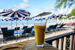 Glass of mango shake with sea view. In Thailand Stock Image