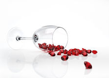 Glass with many red diamonds came out of it Stock Photo