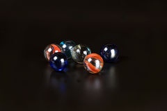 Glass marble ball. On black background spear toy Royalty Free Stock Image