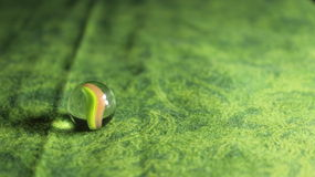 Glass Marble on Green Background Stock Photo