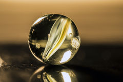 Glass marble macro. Glass marble yellow color inside macro Stock Photography