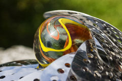 Glass marble in a metal nest. Close-up of a glass marble embedded in a metal nest Stock Image