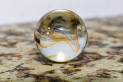 Glass marble with orange and yellow stripes. Macro of a glass marble over a stone granite base, with yellow, blue and orange stripes Stock Image