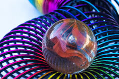 Glass marble in a plastic nest. Macro photo of a glass marble resting in a colourful tube like plastic nest Stock Photography