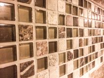 Glass marble tile mosaic. Tile mosaic on the backsplash of a kitchen countertop with brown smoke colored glass, tumbled marble, and granite materials, in neutral Stock Image