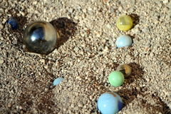 Glass marbles. Colored glass marbles on sand stock image