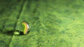 Glass marmor på grön bakgrund Arkivfoto