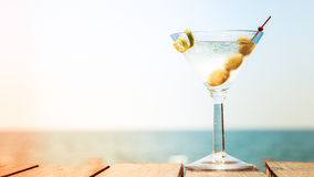 Glass of martini bianco at the wooden pier. Concept of summer va. Cation. Popular cocktail by the sea. Vacation background. Horizontal, wide screen format, toned Royalty Free Stock Photos