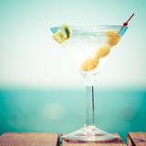 Glass of martini bianco at the wooden pier. Concept of summer va. Cation. Popular cocktail by the sea. Vacation background. Square, toned Stock Image