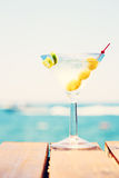 Glass of martini bianco at the wooden pier. Concept of summer va. Cation. Popular cocktail by the sea. Vacation background. Vertical, toned Royalty Free Stock Photo