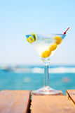 Glass of martini bianco at the wooden pier. Concept of summer va. Cation. Popular cocktail by the sea. Vacation background. Vertical Stock Photos