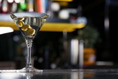 Glass of martini cocktail with olives on bar counter. Space for text royalty free stock photography