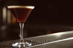 Glass of martini espresso cocktail on bar counter. Space for text royalty free stock image