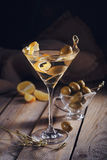 Glass of martini with green olives on a old wooden table Royalty Free Stock Image