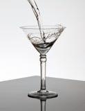 glass martini hällande vatten fotografering för bildbyråer