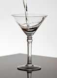 glass martini hällande vatten Royaltyfri Fotografi