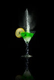 Glass of martini with lime and splashes. At the black background Royalty Free Stock Photo