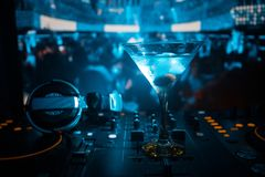 Glass with martini with olive inside on dj controller in night club. Dj Console with club drink at music party in nightclub with d. Isco lights stock photography