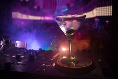 Glass with martini with olive inside on dj controller in night club. Dj Console with club drink at music party in nightclub with d stock photography